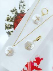 Conjunto colar e brinco madrepérola cruz central pedra micro zircônias transparentes cravejadas.